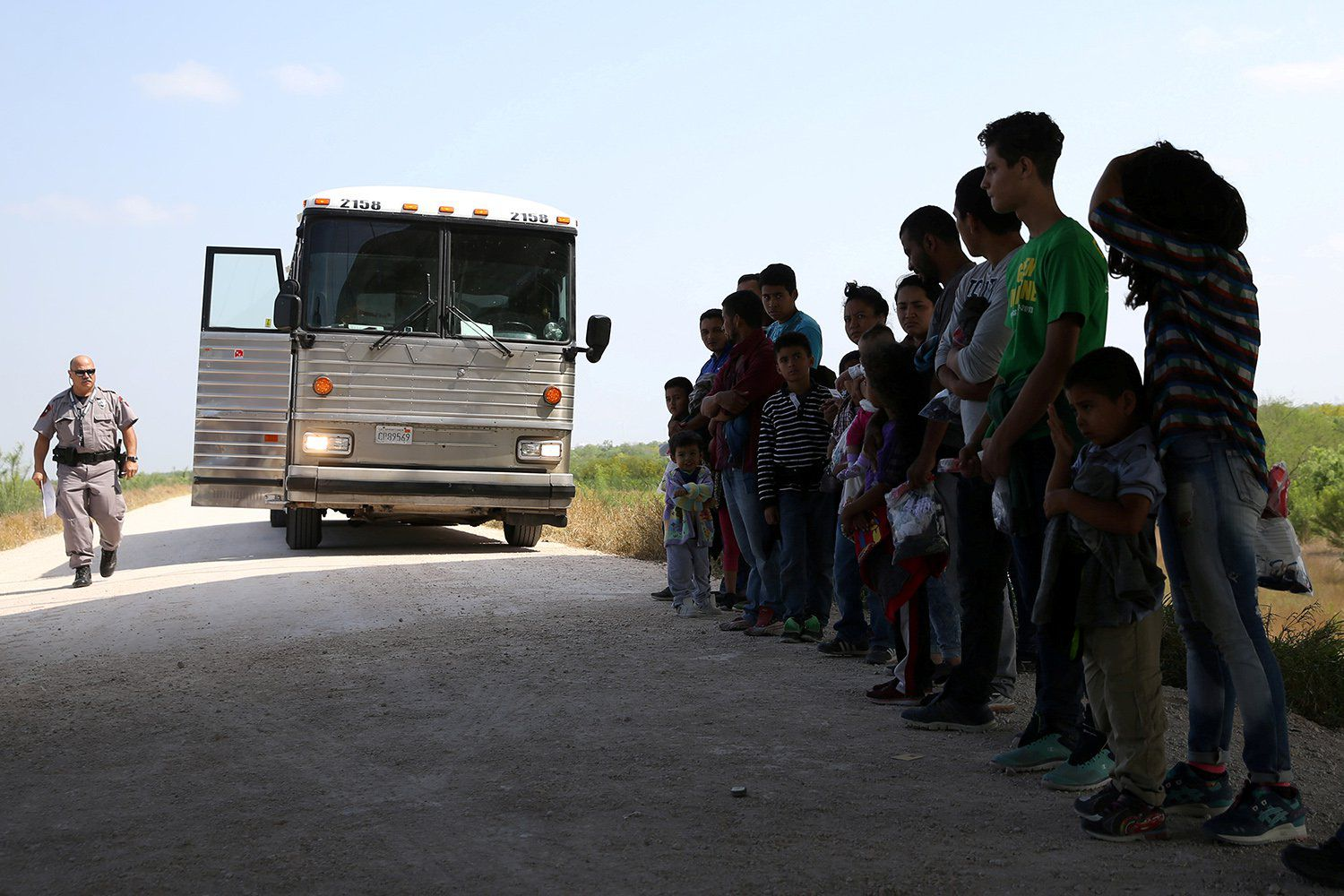 Immigrants who turned themselves in to border patrol agents after illegally crossing the border from Mexico into the U.S. wait to be transported for processing in the Rio Grande Valley sector, near McAllen, Texas on April 2, 2018.
