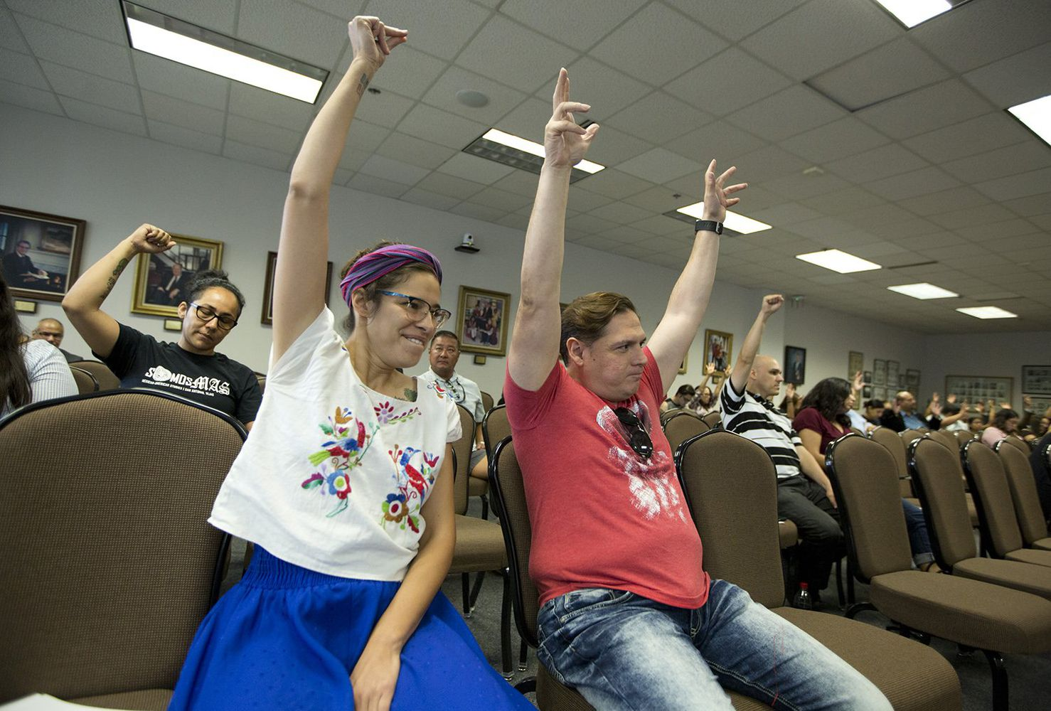 """Devyn Gonzales and Gilberto Sanchez raise their arms in support of changing the name of a new course on Mexican-American history to """"Mexican-American Studies"""" at a State Board of Education hearing on Tuesday."""