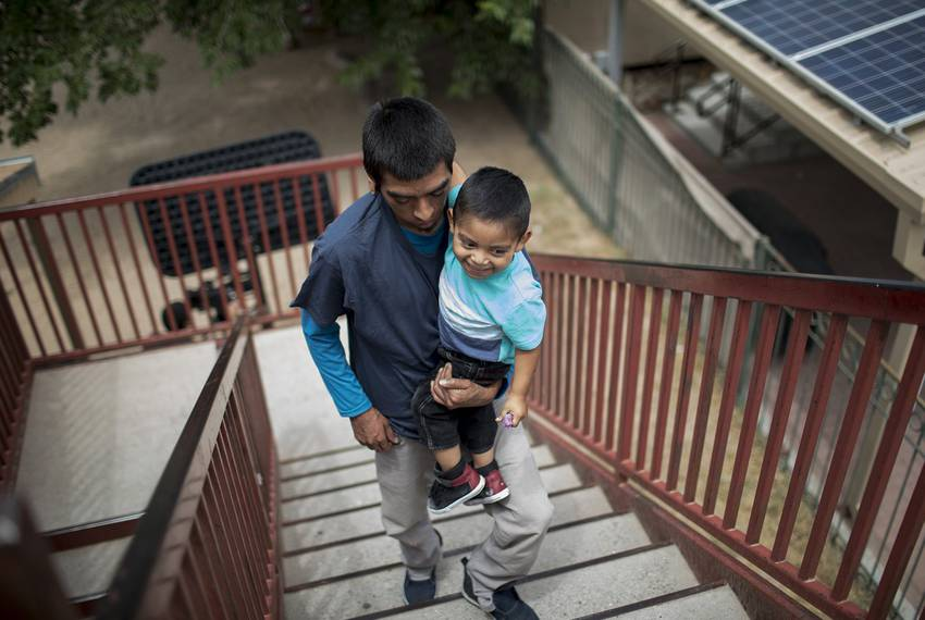 Pablo Ortiz and his son Andres of Guatemala walk upstairs at the Annunciation House in El Paso on July 11, 2018. Ortiz and his son were separated by ICE in April and were reunited and released the night before.