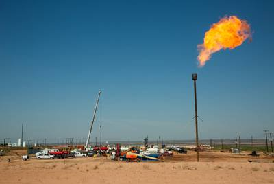 A flare burns on May 24, 2018, atop a drill pad on land near Carlsbad. The oil-rich Permian Basin straddles West Texas and southeastern New Mexico.