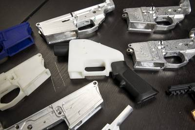Gun parts at Defense Distributed, a Texas-based company developing and publishing open source gun designs for 3-D printing and manufacture, surround a copy of The Liberator, a 3D printed plastic gun.