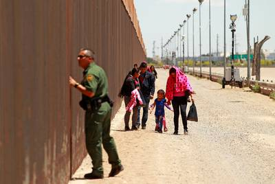 A group of Central American migrants walks next to the U.S.-Mexico border fence after they crossed the borderline while a Border Patrol agent looks through the fence in El Paso, Texas, U.S May 15, 2019.