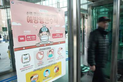 A man walks past a notice for passengers about new coronavirus that has broken out in China, at Seoul railway station in Seoul, South Korea on Jan. 23, 2020.