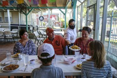 Elia Montoya serves breakfast dishes to U.S. Rep. Chip Roy, R-Austin, and his family at Juan In A Million in East Austin.