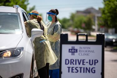 Nurse Kristen Howell, left, and Medical Lab Tech, Amanda Hernandez, administer a COVID-19 test at the Austin Regional Clinic drive-up testing site in Kyle on March 31, 2020.