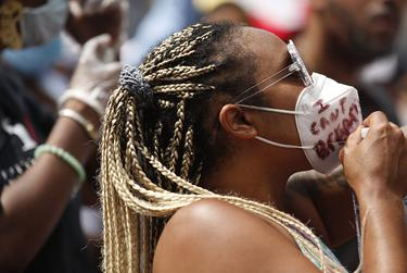 """Alea Rolison wears a mask that reads, """"I can't breathe,"""" at a rally for George Floyd in Houston, Texas."""