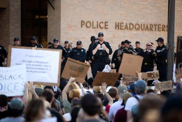 Police look on demonstrators gathered outside Austin Police headquarters for another night of protest against police violence towards people of color on Thursday.