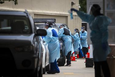 Healthcare workers collect self-swab COVID-19 tests at a testing site in the Fifth Ward in Houston.
