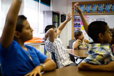 Science students at Bayless Elementary in Lubbock raise their hands to answer a question posed during a water conservation presentation.