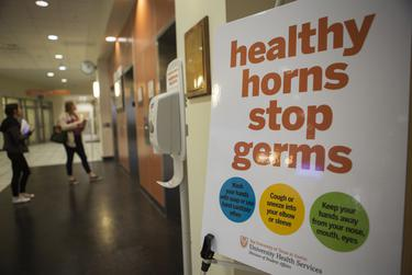 A sign in the University of Texas at Austin's Student Services Building shows information on how to prevent the spread of airborne illnesses.