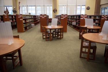 Partitions sit on a table in the library at Judson High School on Tuesday, Aug. 11, 2020 in Converse. The librarian purchased the partitions with her own funds for $7.50 each. In the background, aisles of books are blocked off to control the flow of traffic through the library.