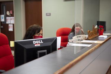 Receptionists work behind a plexiglass barrier in the front office, one of the only areas with plexiglass installed, at Judson High School Tuesday, Aug. 11, 2020 in Converse.