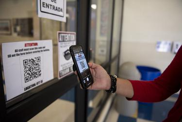 Principal Madeline Bueno demonstrates how staff and visitors are required to scan a code and fill out a form before entering the building at Ott Elementary School on Tuesday, Aug. 11, 2020 in San Antonio. The form asks if staff or visitors have experienced any COVID-19 symptoms recently.