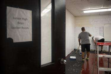 Coaches paint a locker room at Premont Collegiate High School on Tuesday, Aug. 4, 2020 in Premont. The locker room is being transformed into a meeting space for students and coaches.