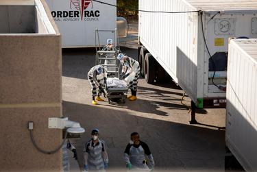 """El Paso County detention inmates, also known as """"trustees"""" (low level inmates) help move bodies to mobile morgue units outside the Medical Examiner's Office on Nov. 14, 2020. Due to the recent COVID-19 surge of positive cases and deaths in recent weeks in El Paso, the Medical Examiner's Office has asked the jail for help."""