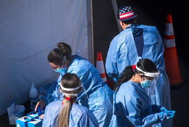 Medical personnel put on personal protective equipment at a COVID-19 testing site at the University of Texas at El Paso on Election Day in El Paso on Tuesday, Nov. 3, 2020.