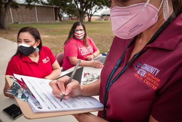 Nelissa Ortiz of Community Action Health Center signs up a patient for a flu shot. Nov. 13, 2020