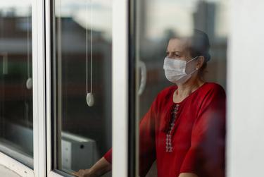 A person looks out their window during the COVID-19 pandemic.