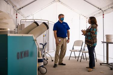 David Lee, Chief Executive Officer, speaks with Barbara James inside a tent set aside for triaging COVID-19 patients located just outside the ER ambulance bay at Otto Kaiser Memorial Hospital in Kenedy.