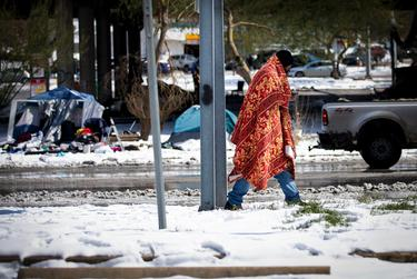 A person walks past tents near the Interstate-35 frontage road  in Austin on Feb.16, 2021. A winter storm caused icy roads and left millions of Texans without water or electricity.