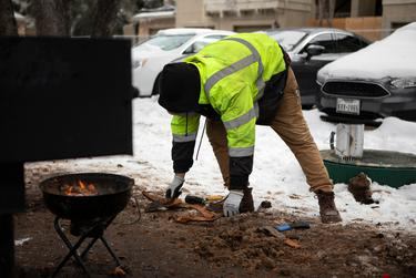 Jacob Duran prepares wood for a grill. Duran has been cooking meals outsides after his apartment lost power. Feb. 18, 2021.
