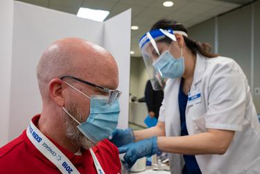 Dave DeJohn, a teacher at Yates High School, gets vaccinated by pharmacist Ilana Druker at Houston Independent School District's Hattie Mae White Educational Support Center on Jan. 9, 2020, in Houston.