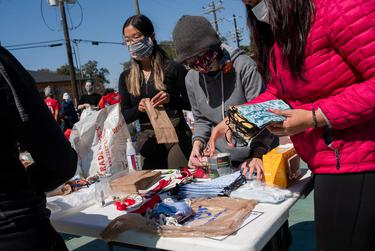 From left: volunteers Anjie Zhi, Karina Barbosa and Jessica Porras prepare masks at Kelly Village, a supply distribution site, on Feb. 19, 2021, in Houston.