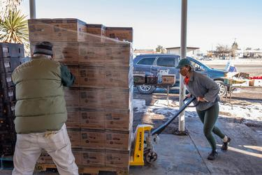 Marfa Food Pantry volunteers Gary Oliver and Alisha Waller load pallets with boxes of food for Saturday morning distribution. West Texas Food Bank delivered food Friday night after power was restored in Marfa.