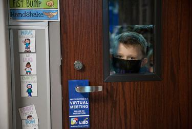 Levi Pedrick peaks out of his kindergarten class window on the first day of in-person classes at Highland Village Elementary.
