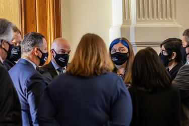 """A group of House democrats wearing masks with the slogan """"Good Trouble,"""" referencing the late civil rights leader John Lewis, meets in the House floor corner on May 6, 2021."""